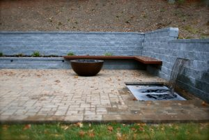 Stone patio with sheet water feature and stone fire pit